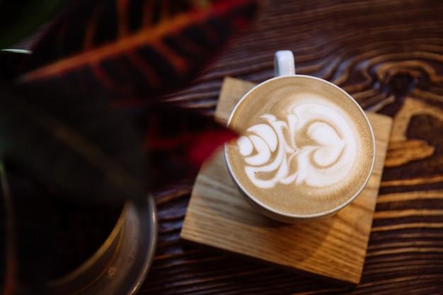 Koffiekopje met latte kunst op houten tafel. naast de beker staat een levende ficusbloem
