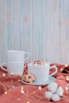 Koffiekopje met marshmallow en sterrenkoekjes op warme gebreide koraaldeken, kerstverlichting en katoenbloemen.
