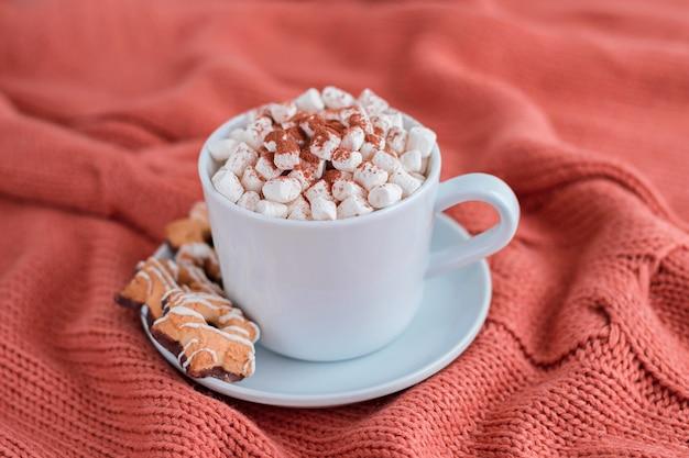 Koffiekopje met marshmallow en sterrenkoekjes op warme gebreide koraaldeken.