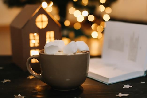 Koffiekopje met marshmallows en een boek op tafel. stilleven op donkere achtergrond, plat leggen