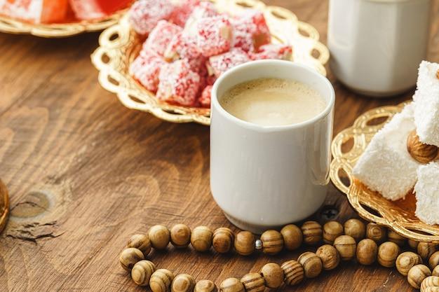 Koffiekopje met oosterse snoepjes op houten tafel close-up