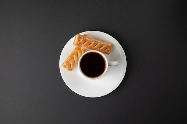 Koffiekopje met snoepjes op grijs