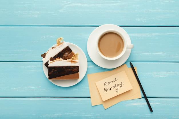 Koffiekopje met stukjes cake en notitie goedemorgen op blauwe rustieke tafel van bovenaf. bovenaanzicht op gezellig en smakelijk ontbijt, kopieer ruimte