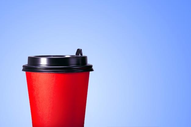 Koffiekopje om op blauwe achtergrond met exemplaarruimte te gaan.