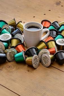 Koffiekopje omgeven door gebruikte koffiecapsules op houten tafel