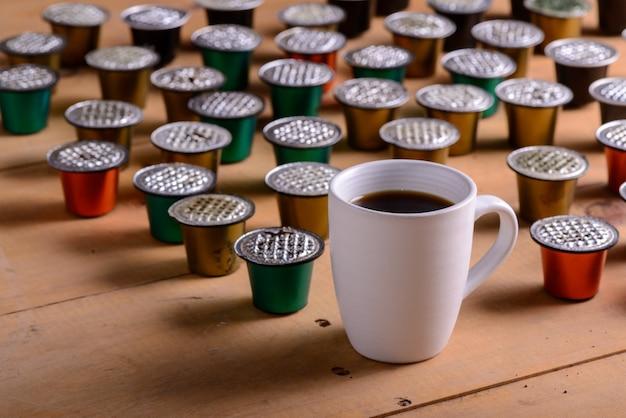 Koffiekopje omgeven door gebruikte koffiecapsules op houten tafel Premium Foto