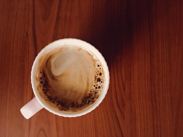 Koffiekopje op houten bureau, plat lag achtergrond en zakelijke mockup, bovenaanzicht