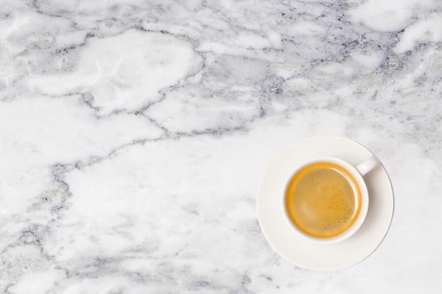Koffiekopje op marmeren tafelblad bekijken.