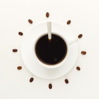Koffiekopje op schotel en geroosterde bonen gerangschikt als wijzerplaat op witte geïsoleerde achtergrond, bovenaanzicht. koffie tijd symbool. energie en verfrissing concept, kopieer ruimte
