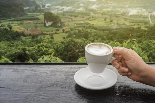 Koffiekopje op tafel met uitzicht op de bergen in de ochtend als achtergrond