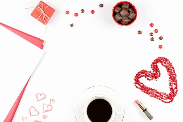 Koffiekopje, snoepjes, lippenstift, hartvorm en geschenkdoos op witte achtergrond. valentijnsdag concept frame.