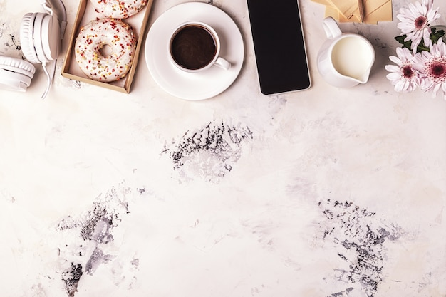 Koffiekopje, telefoon en koptelefoon