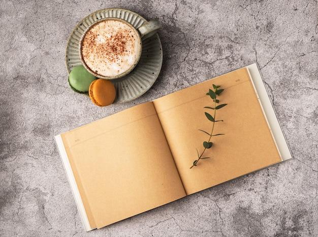 Koffiekopje voor ontbijt, bitterkoekjes, lege notebook op een grijze betonnen tafel