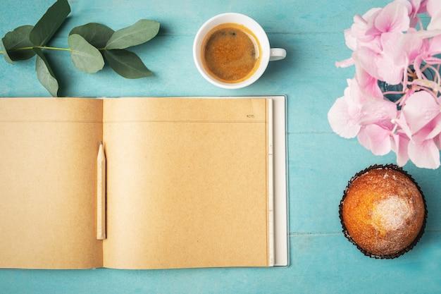 Koffiekopje voor ontbijt, cupcake, leeg notitieboekje, tak met eucalyptusbladeren en en roze hortensia,