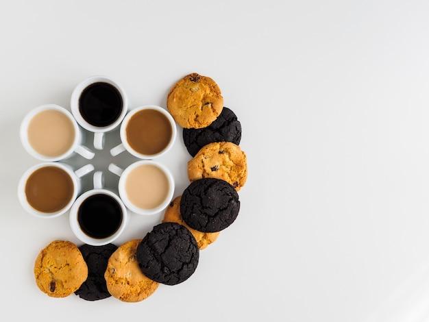Koffiekoppen geplaatst in een cirkel en verschillende koekjes