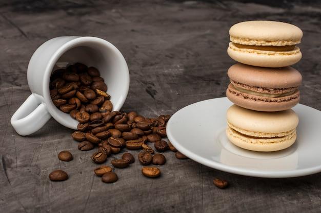 Koffiekorrels gemorst uit een witte kop tegen een donkere achtergrond