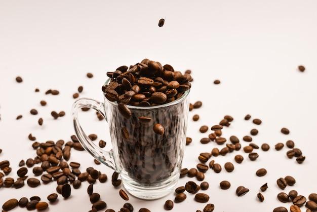 Koffiekorrels worden in een glazen beker op een wit oppervlak gegoten
