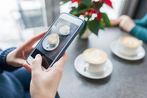 Koffiekunst, handen van vrouw die foto's op de telefoon nemen