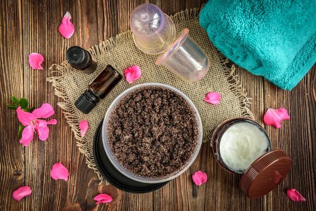 Koffielichaamsscrub, suiker en kokosolie, etherische oliën, vacuümmassagepotten op donkere houten rustieke tafel met roze bloemen.