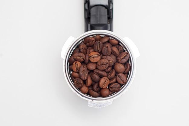 Koffiemachine filterhouder met koffiebonen op wit bord.