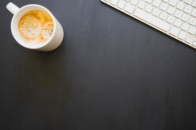 Koffiemok een toetsenbord op een donker bureau
