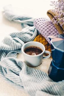 Koffiemok en blauwe geiser koffiepot op een witte sprei, een stapel gebreide kleding