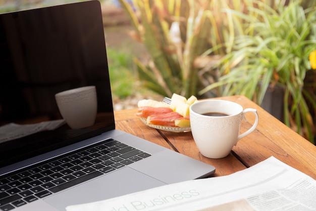 Koffiemok en krant met vers fruit en laptop op houten lijst.
