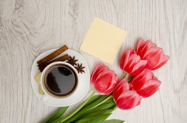 Koffiemok met kruiden, schone notitie, roze tulpen op een houten, lente ontbijt