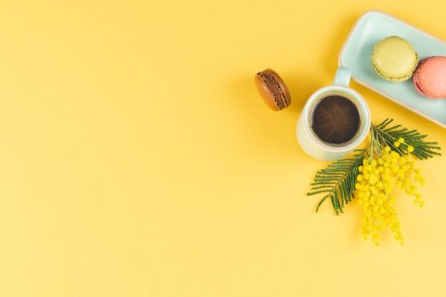 Koffiemok met macarons en gele bloemendecoratie op geel. bovenaanzicht.