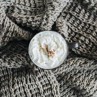Koffiemok met slagroom en kaneelpoeder
