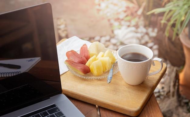 Koffiemok met vers fruit en laptop op houten lijst in de tuin.