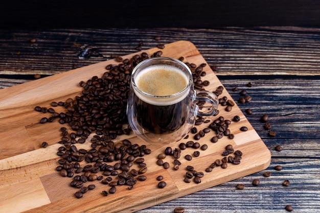 Koffiemok op een houten bord en koffiebonen