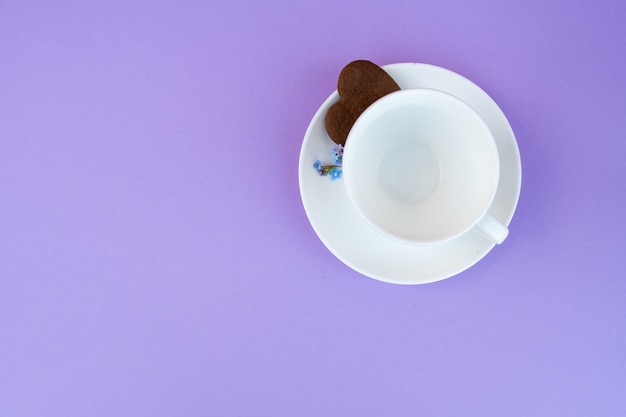 Koffiemok op een paarse achtergrond. achtergrond ontbijt, drankjes en cafe menu concept - koffiekopje op paarse achtergrond, flatlay toplay. koekjes voor koffie. witte mok. kopieer ruimte