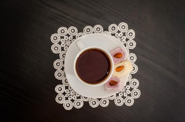 Koffiemok op schotel met turks fruit op een zwarte tafel, bovenaanzicht