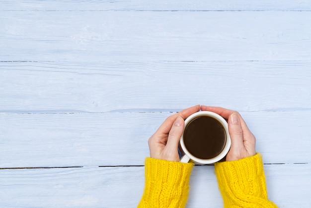 Koffiemok ter beschikking op de oude houten mening van de lijstbovenkant met exemplaarruimte. vrouw in gezellige gele huissweater met een mok koffie onder het genot van een drankje