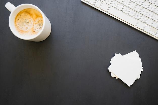 Koffiemok, visitekaartjes en toetsenbord