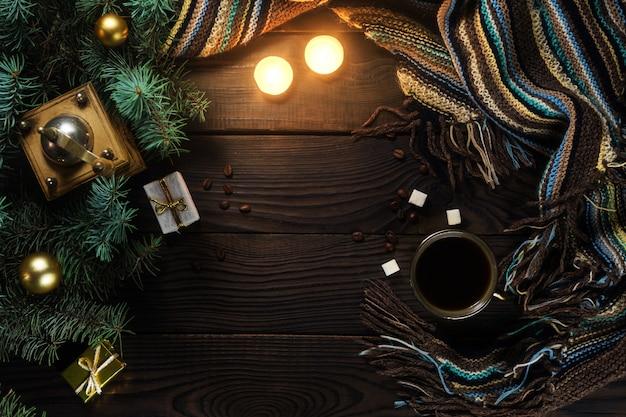 Koffiemolen, beker, kaarsen en kerstboom op een houten tafel. bovenaanzicht