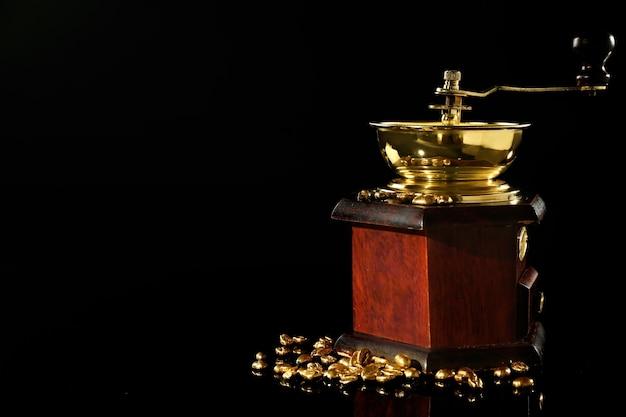 Koffiemolen met gouden bonen op zwart