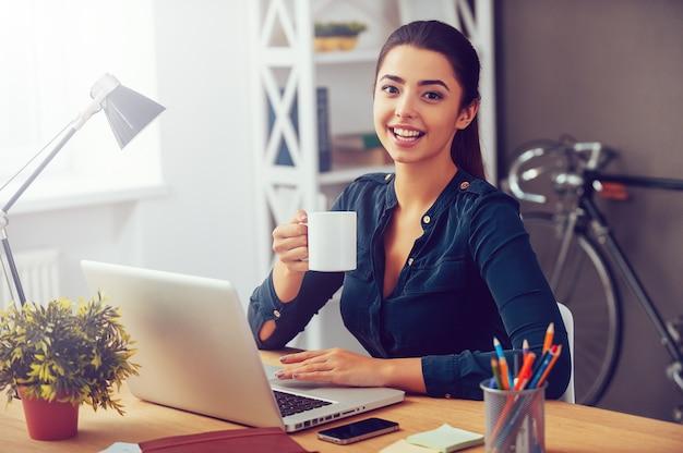 Koffiepauze. aantrekkelijke jonge vrouw die een koffiekopje vasthoudt en glimlacht