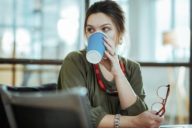 Koffiepauze. donkerharige succesvolle zakenvrouw die zich opgelucht voelt tijdens een koffiepauze op kantoor