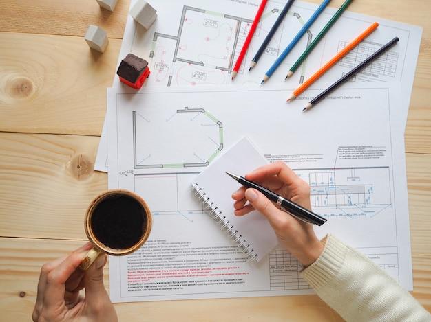 Koffiepauze, een kopje koffie tijdens een pauze op het werk. het bedrijfsconcept van bouwschema's in een architectenbureau.