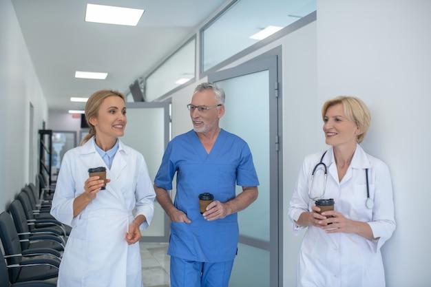Koffiepauze. groep glimlachende artsen die van koffie in de gang genieten