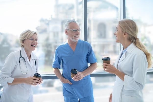 Koffiepauze. groep lachende artsen koffie drinken naast het raam, met een vriendelijk gesprek