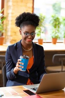 Koffiepauze hebben. vrolijke krullende interieurontwerper met koffiepauze en e-mail lezen op laptop