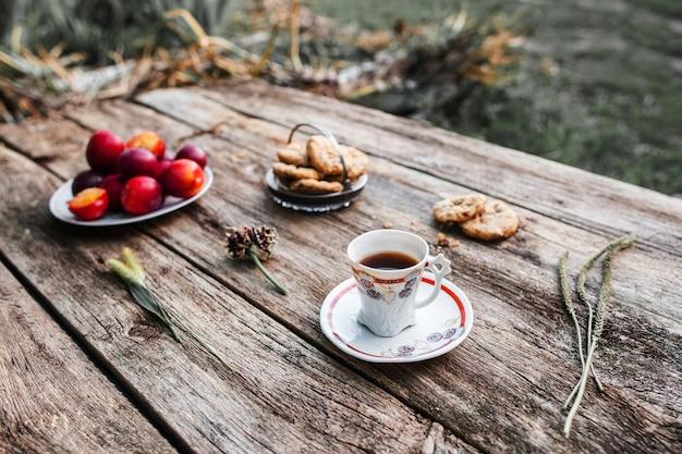 Koffiepauze in dorp, rust van verstedelijking. oude rustieke houten tafel met kopje koffie, koekjes en pruimen. ontbijt in de natuur.