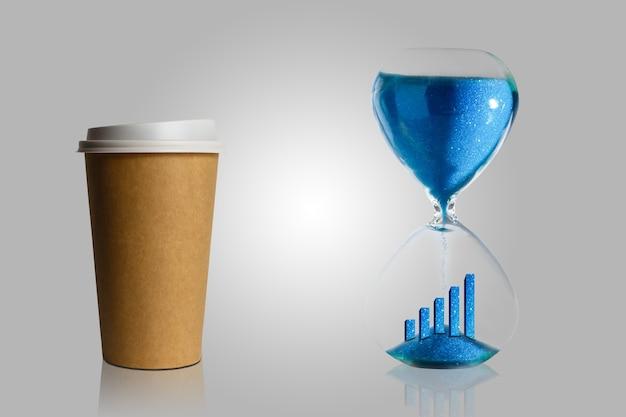 Koffiepauze in het proces, koffie in een papieren beker en zandloper blauwe achtergrond. abstract.
