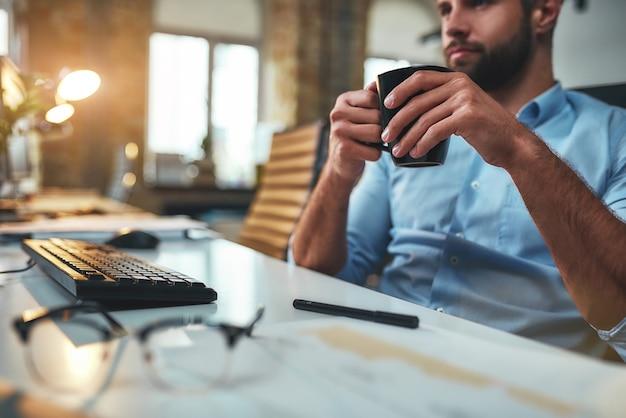 Koffiepauze jonge, bebaarde zakenman in formele kleding die koffie drinkt en naar de computer kijkt terwijl