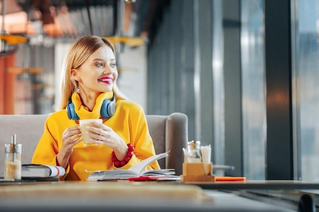 Koffiepauze. mooie jonge blonde zakenvrouw die geniet van haar koffiepauze