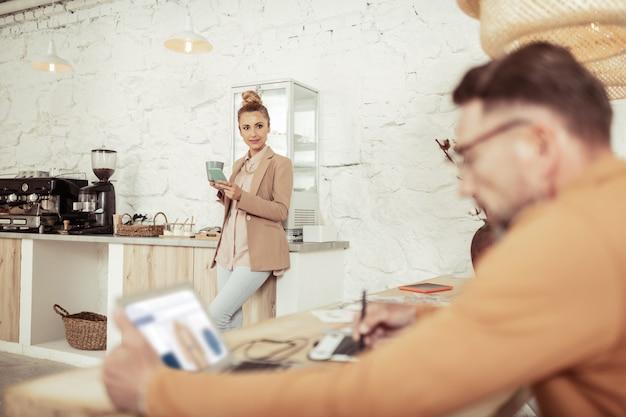 Koffiepauze. mooie vrouw met haar smartphone en een kopje koffie in de buurt van de koffiemachine en kijkend naar haar baas.
