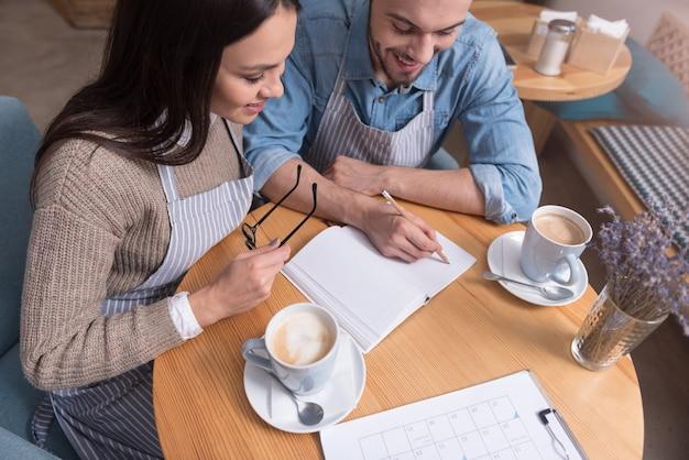 Koffiepauze. positieve jonge charmante paar café-eigenaren die thee drinken en glimlachen terwijl ze aan tafel werken.